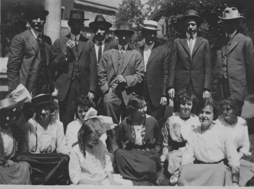 Group - men standing - women seated on ground